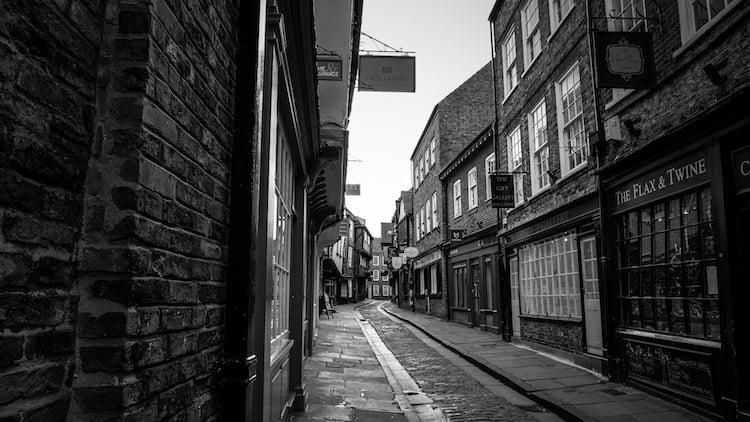 The Shambles Alleywau in York taken in black and white. A narrow dark alley with a large groove down the middle.