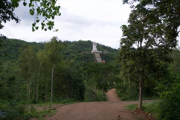 A red sand road leading up to some steps where at the top is a giant Buddha statue