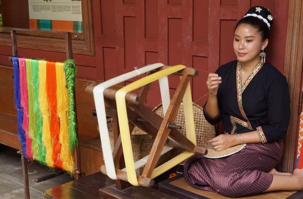 A Thai lady sitting down with her legs underneath her spinning silk. She has 8 colours of silk on a loom beside her.