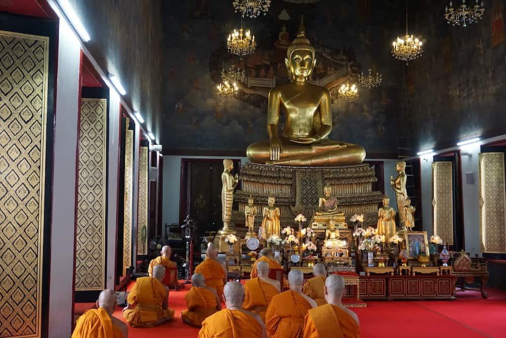Monks in orange robes meditating in front of a giant golden Buddha at Golden Mount, Bangkok