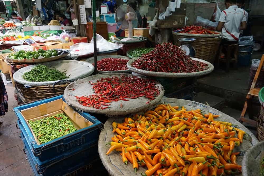 Huge plates of chillis at Pak Khlong market in Bangkok. There are oranges, red and green chillies of different varieties piled up to huge heights.