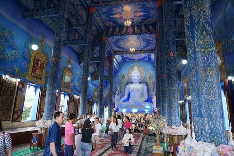 A very blue interior of a temple. People worshipping a giant Buddha which is lit up with blue lights.