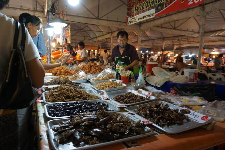 Man serving insects at night market in Chiang Mai, Thailand