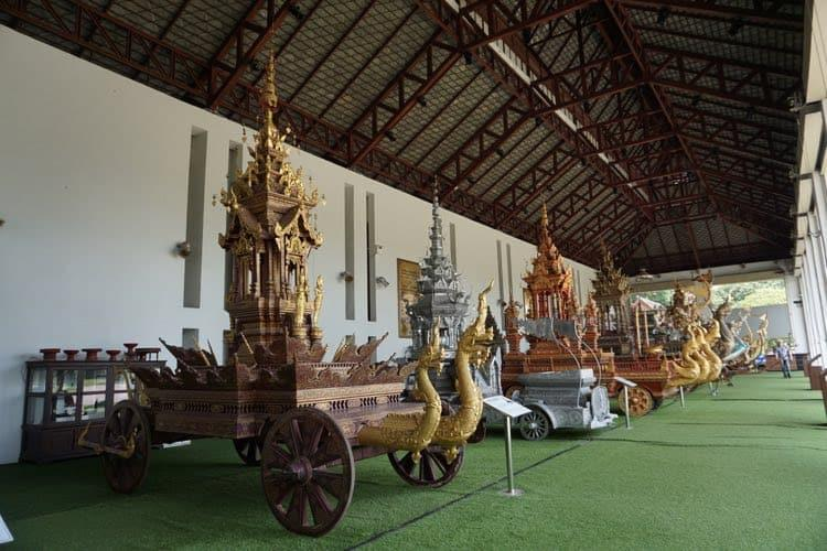 A line up of traditional Royal chariots, in a giant barn with green carpet
