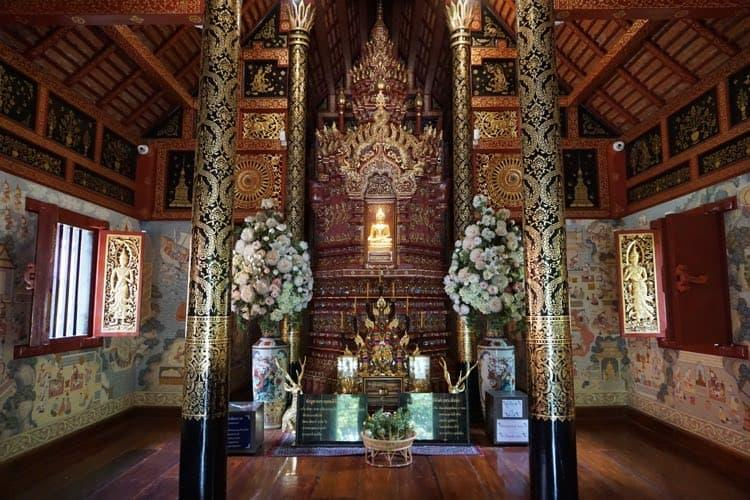The inside of Wat Phra Singh temple. A wooden temple with two giant pillars either side of an ornate shrine, wood with lots of gold.