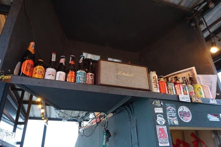 A shelf in a rooftop bar with lots of craft beers and a Marshall amplifier