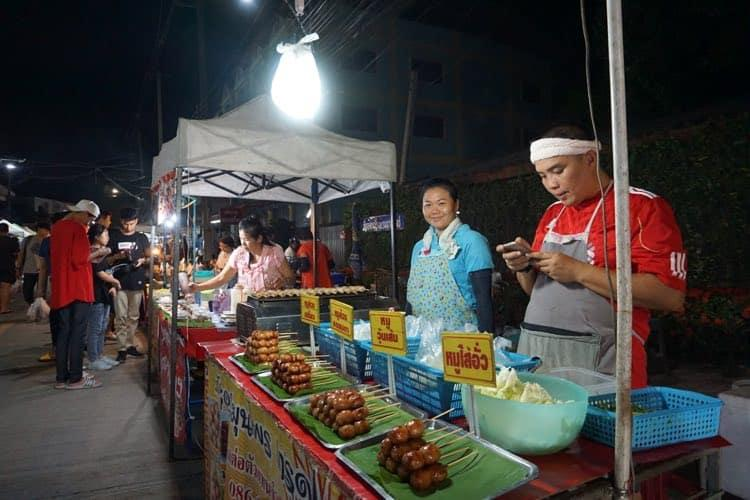 A man on his cellphone at a night market stall selling pork on sticks