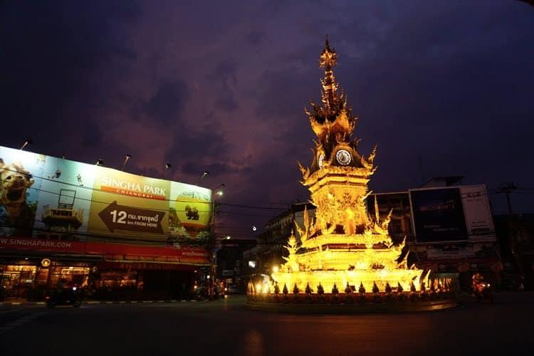 a golden clock tower on a roundabout, lit up. The sky behind is purple