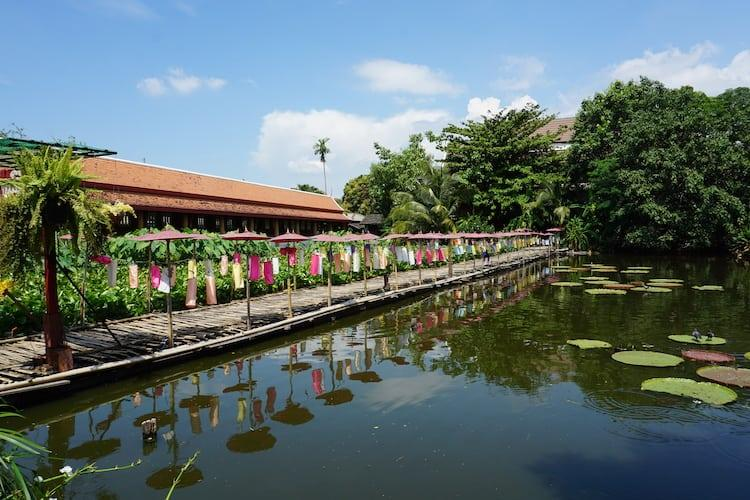 A carp pond with colourful flags at Wat Jedlin in Chiang Mai