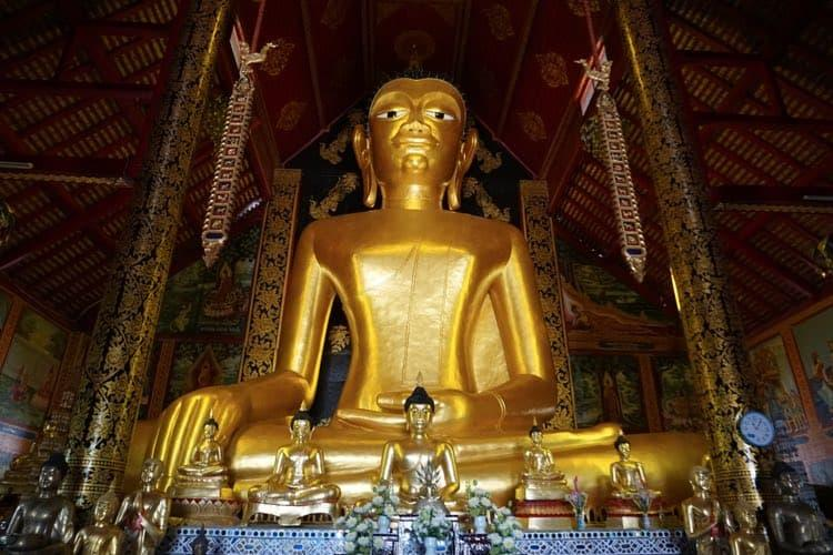 A huge golden Buddha statue with 11 mini statues in front of it.