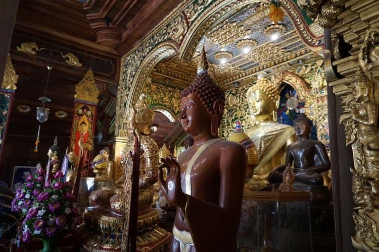 A traditional Buddha image carved from wood with a golden Buddha behind it.
