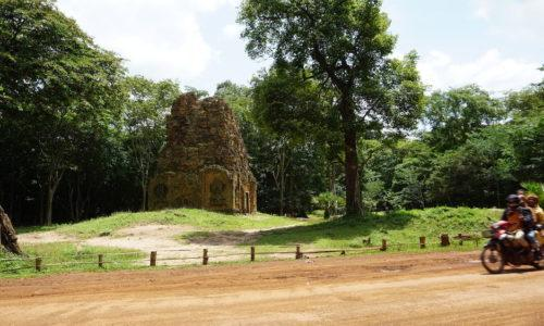 A temple at Sambor Prei Kuk, Cambodia with a motorbike driving past