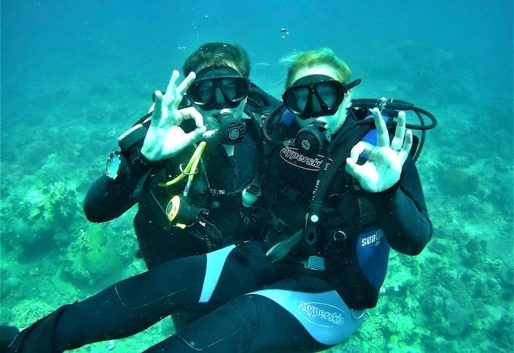 Two people doing the 'ok' sign whilst scuba diving.