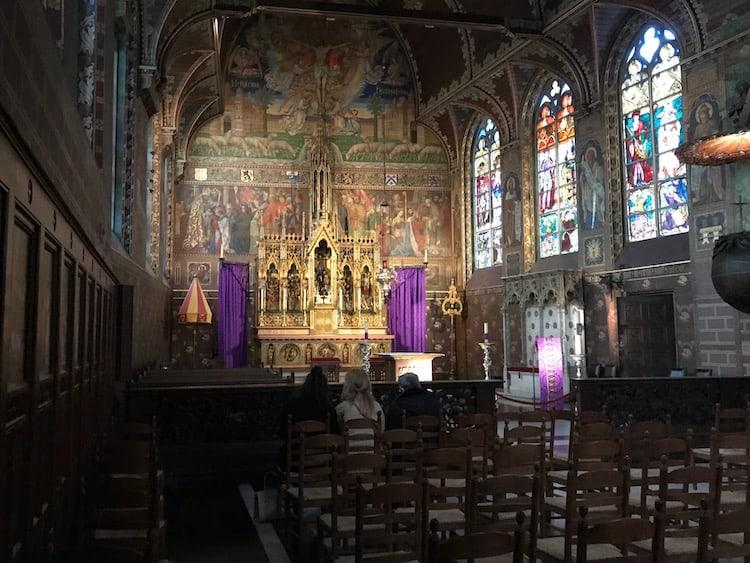 Inside the basilica of the Holy Blood in Bruges. A golden altar flanked by purple curtains with stained glass windows to the right.