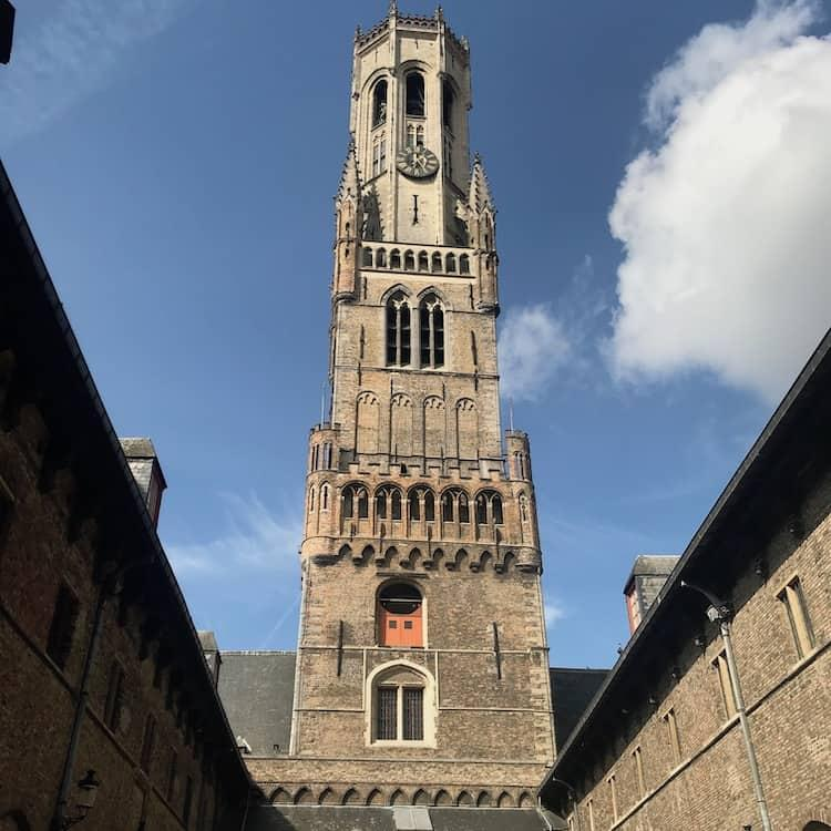 The Belfry of Bruges with blue skies behind