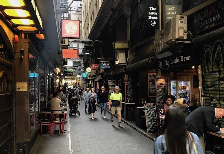 A dark laneway with coffee shops and cafes either side