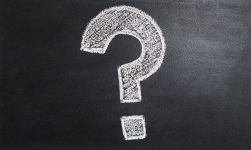 A question mark written in chalk on a blackboard.