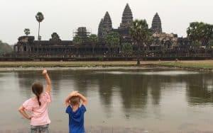 Two kids standing in front of Angkor Wat Temple