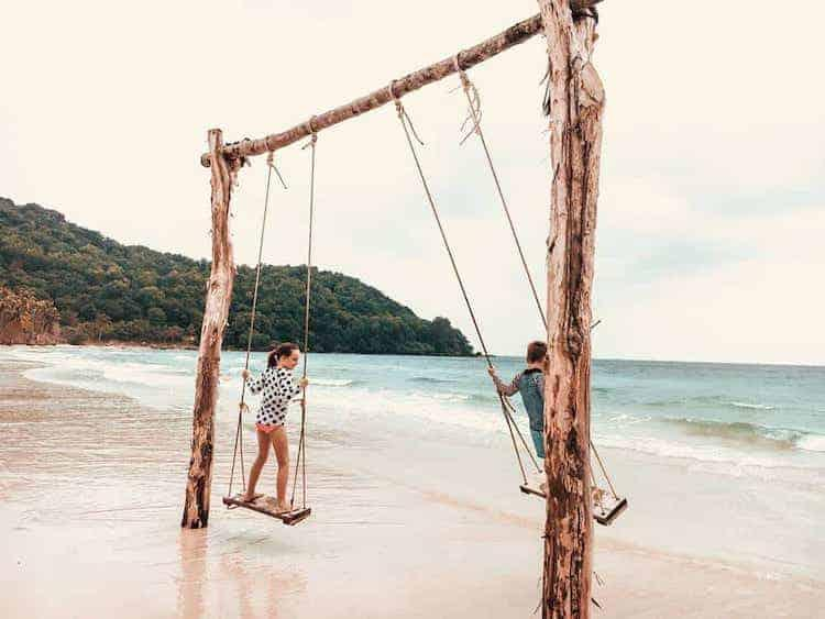 Kids playing own swings at Phu Quoc beach in Vietnam whilst taking a family sabbatical.