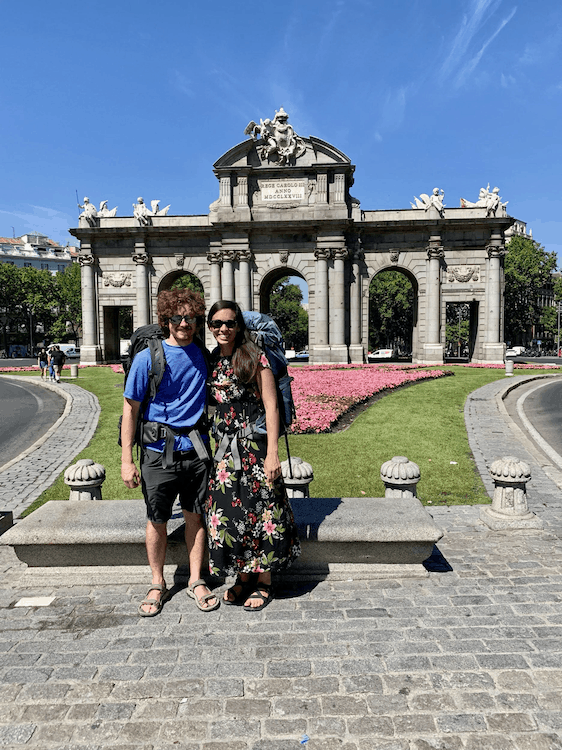 A couple on sabbatical standing in front of a lawn with a pink flower bed and a stone archway monument behind
