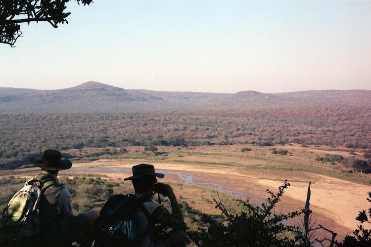 An old scanned in photo of two men looking out over an African plain