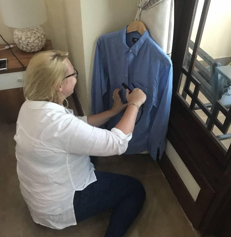 Woman straightening a blue shirt using hair straighteners, a perfect present for someone going travelling