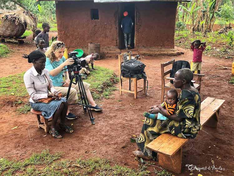 A woman photographing a woman and child on a wooden bench in Uganda