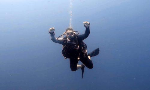 A woman in scuba diving gear doing a thumbs up