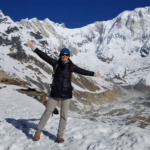 A lady standing at the top of a snowy mountain doing 'jazz hands'