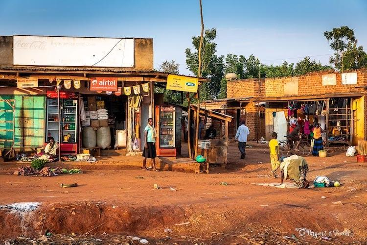 A street scene in Africa, with a dusty road and shop.