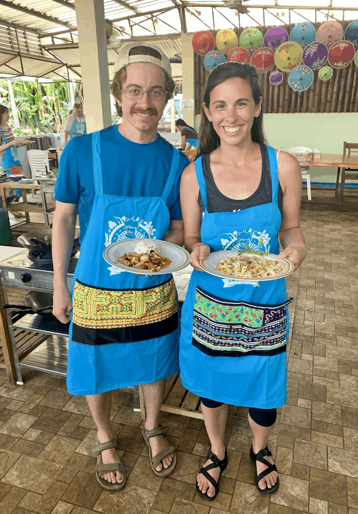 A man and women wearing blue aprons holding plates of food they have made whilst on a cooking course in Asia