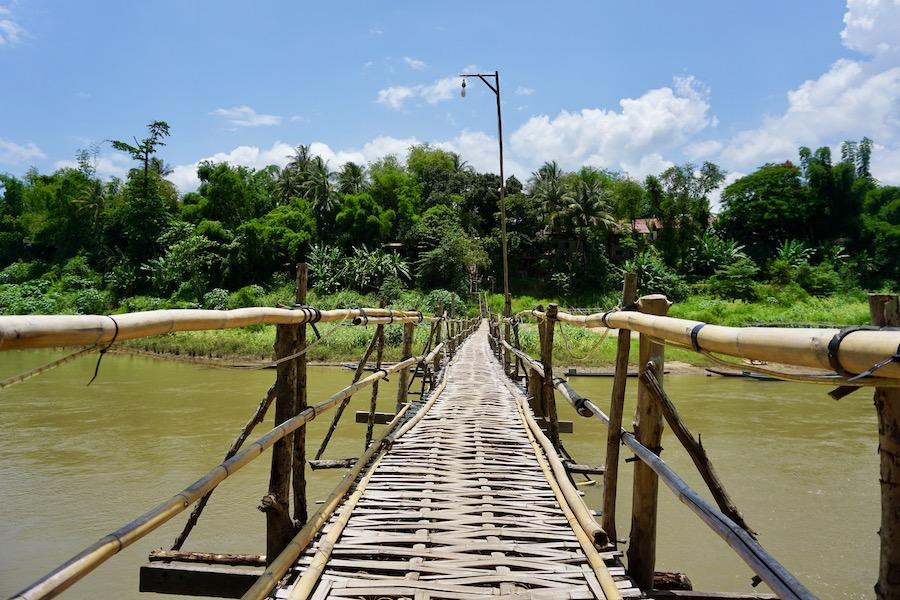 a bamboo bridge over a dirty brown river with blue sky in the distance