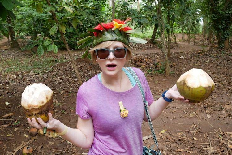A woman in a pink t-shirt holding two coconuts
