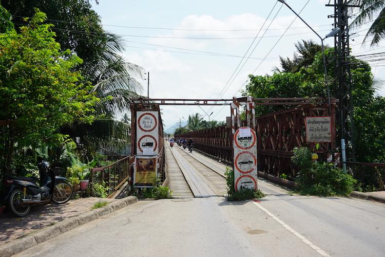 The entrance to an old Bridge in Luang Prabang. Red metal with wooden planks down the middle