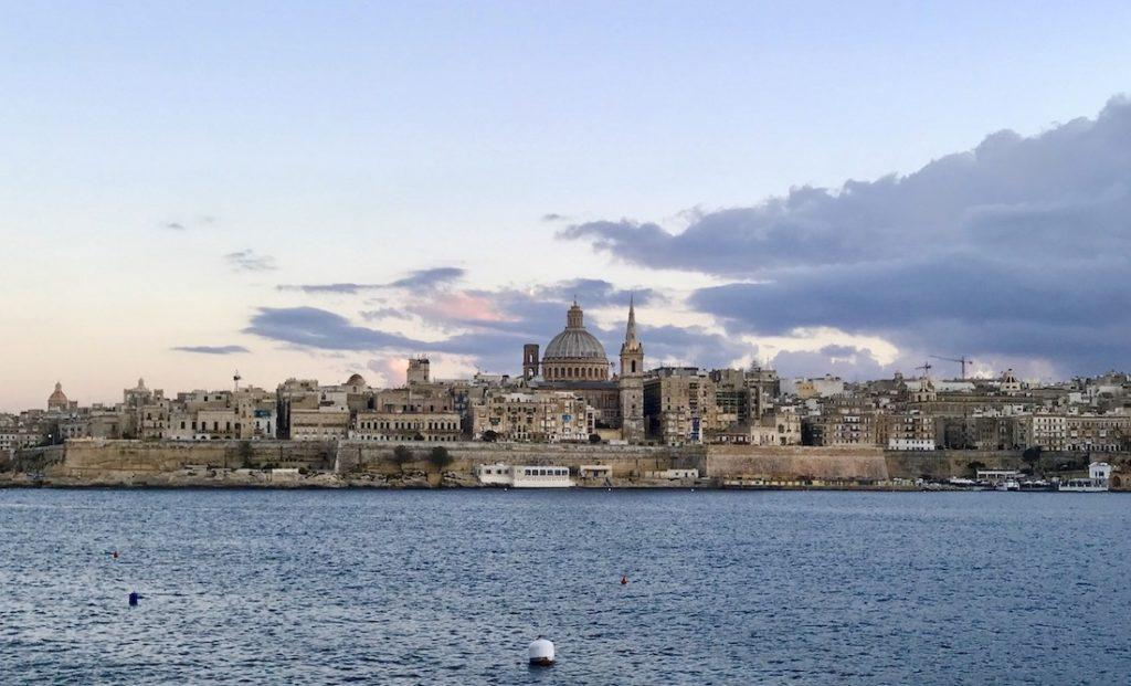 An image of Valletta in Malta with the sun setting in the background