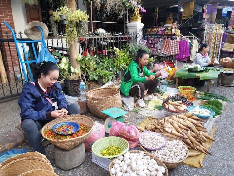 Three ladies sitting amongst displays of vegetables in a morning market in Luang Prabang
