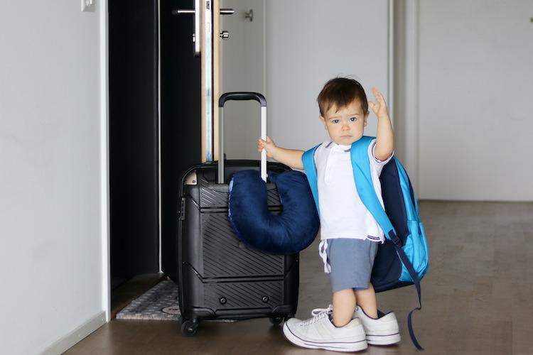 Cute little baby boy in fathers sneakers and with big backpack holding suitcase and waving goodbye staying at open door ready to travel. Traveling with child concept.