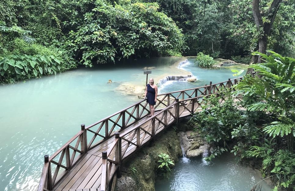 A lady standing on a wooden bridge with turquoise blue waters behind her