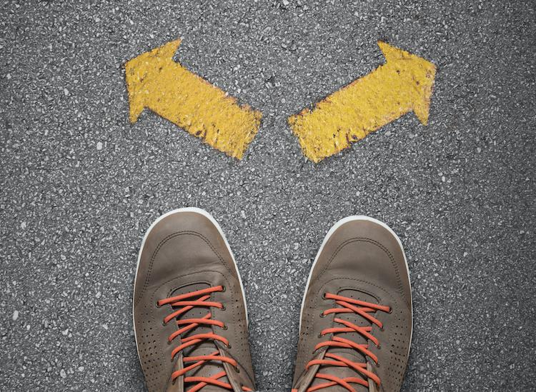 A pair of brown canvas shoes with orange laces on a pavement, with two yellow arrows facing different directions in front of them