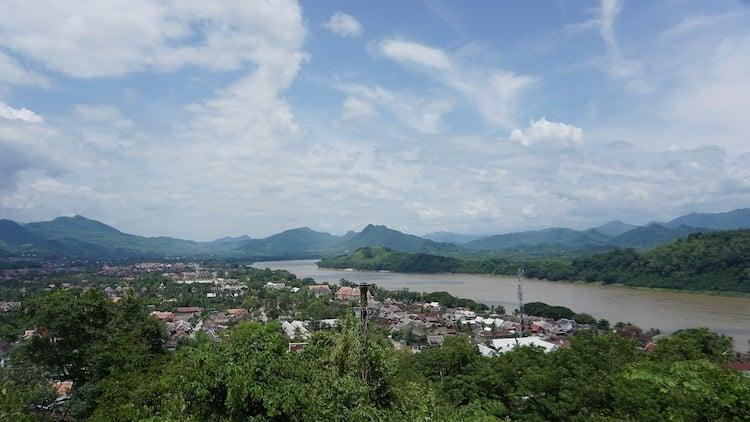 A brown river with blue skies and wispy clouds over lush green trees. The view from Mount Phousi in Luang Prabang