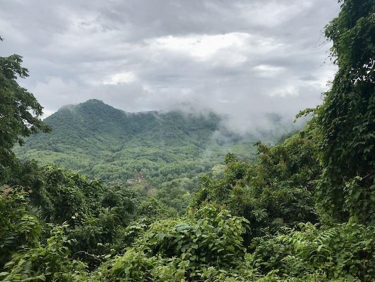A lush green valley in Laos with clouds coming over the mountain opposite