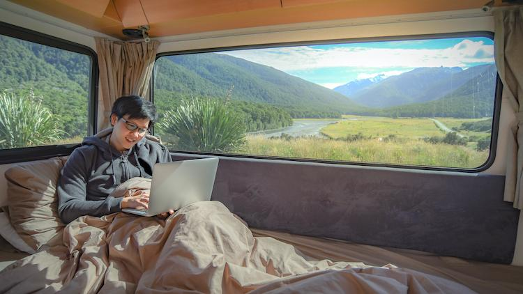 Young Asian man working with laptop computer on the bed in camper van with mountain scenic view through the window, digital nomad on road trip concept