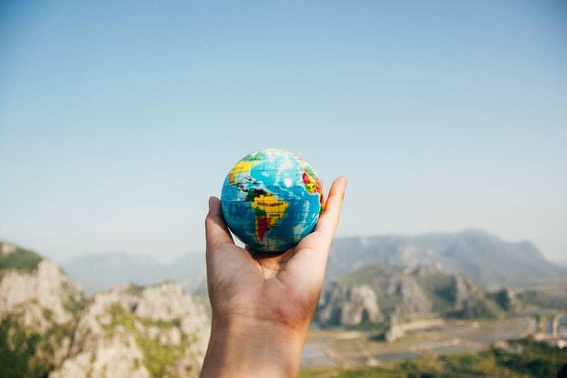 a person holding a small globe in front of some mountains
