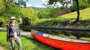 A lady standing in front of a red canoe