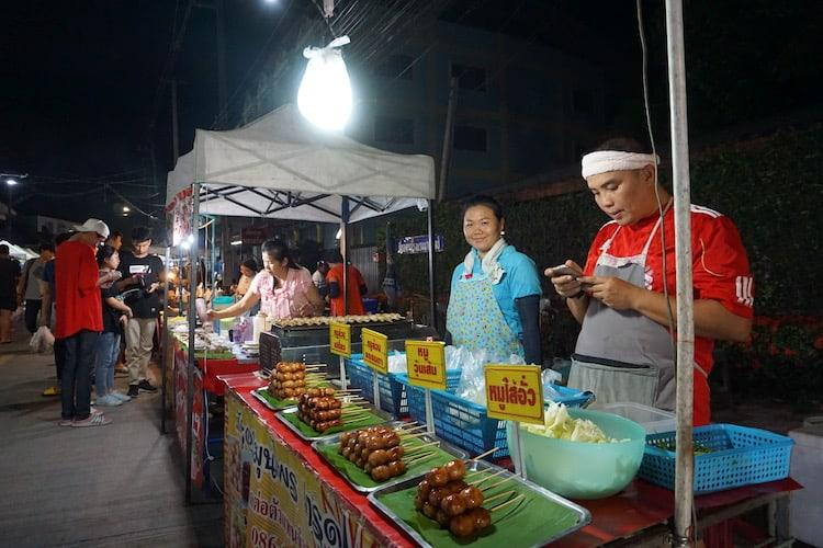 A lady and man stand behind a food stall selling pork on sticks. The man is on his phone, the lady is smiling at the camera.