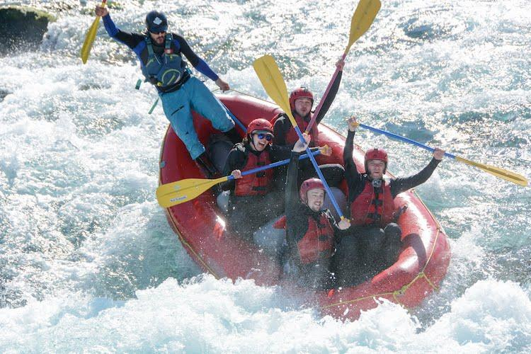 Five people on a red white water raft