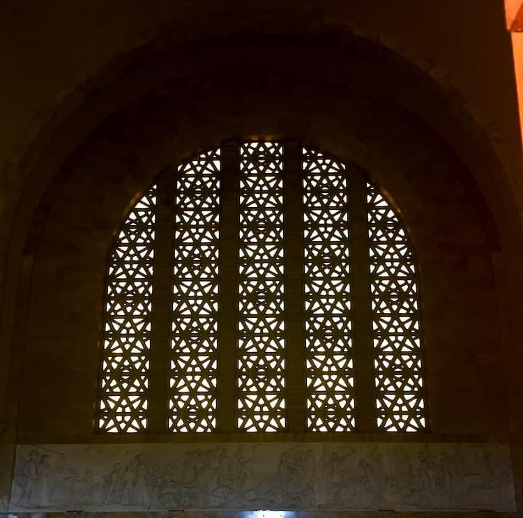 A giant window will with triangle structures and a stone frieze beneath it
