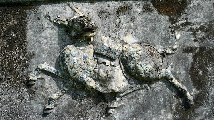 A stone image of a bull, built into a wall and decorate with pieces of coloured ceramic
