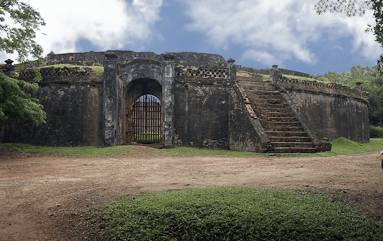 A dark stone arena with gates and stone stairs to the right leading up to the top of the walls.