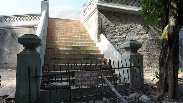 Brick stairs with store balustrades either side which have been refurbished. A metal gate stops people walking up them with a warning sign in Vietnamese